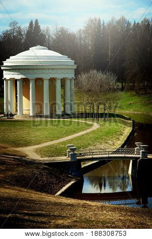 Landscape in the Pavlovsk park in spring, beautiful gazebo with columns , beautiful park with paths and a bridge across a stream, vertical