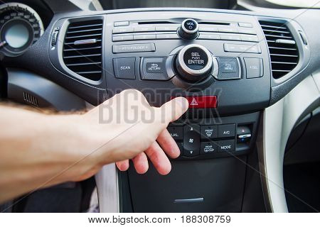 Man pushing emergency light button while driving car. emergency stop.