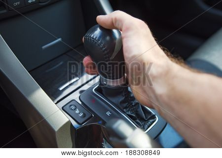 A man's hand on an automatic gearbox. Automatic shift transmission close up.