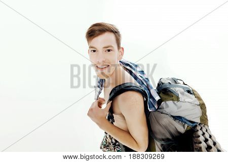 Funny portrait of young hiker with a backpack on a white background