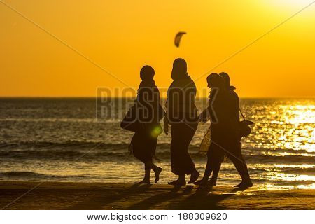 Kijkduin beach the Netherlands - May 26 2017: group of girls walking on beach at sunset during warm weather