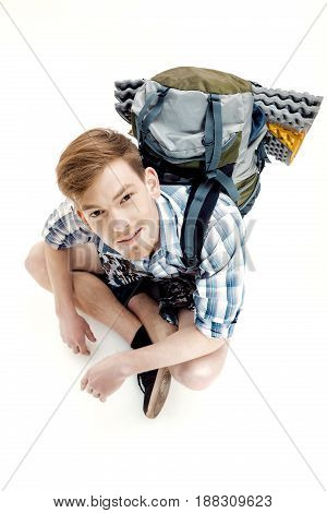 Funny Young tourist is sitting with backpack on the white background. traveler is preparing for hike