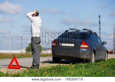 Man stands on road near broken car in afternoon