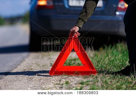 Man puts red warning triangle on road against background of car