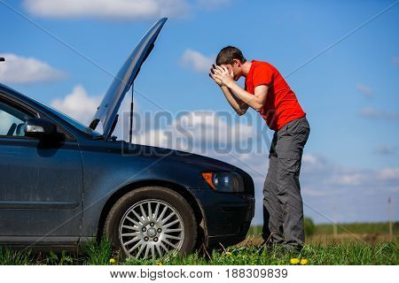Sad man near open hood of car on road during day