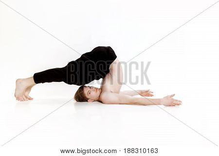 Young man doing yoga exercises. Studio shot on the white background
