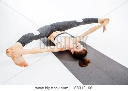 Sportswoman makes twine lying on rug at empty background