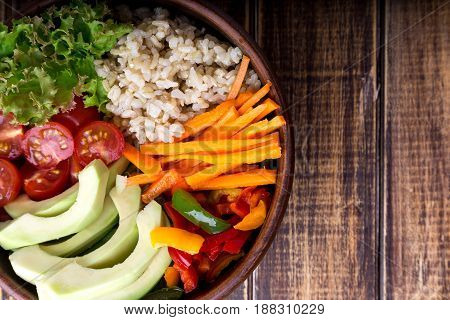 Vegan buddha bowl on wooden background. Top view. Bowl with carrot, lettuce, tomatoes cherry, pepper, avocado and porridge. Vegetarian, healthy, detox food concept