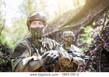 Two soldiers in military helmet and camouflage with gun on forest background