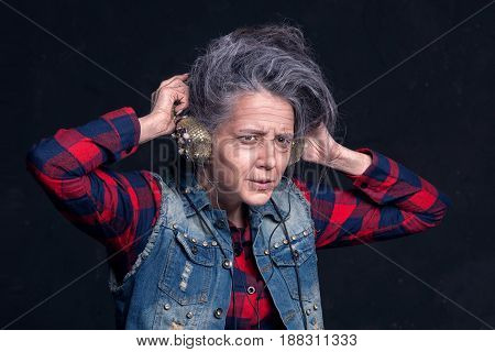 Young Girl With Makeup Of Senior Woman. Elderly Granny Listens To Music In Headphones.