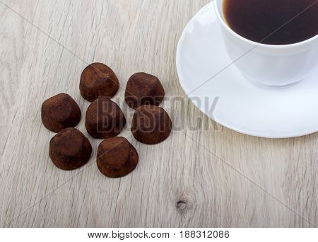 dessert truffle cocoa and coffee cup on a wooden table.