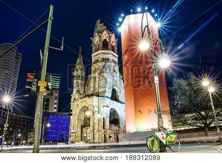 BERLIN GERMANY - APRIL 7: Bicycle under the lamp and ruins of Kaiser Wilhelm Memorial Church which was bombed during World war II on April 7 2017 in Berlin