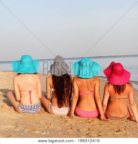 Slender girls are sitting on the beach. Back view