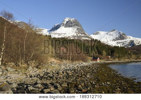 Seashore with stones in foreground and mountains with snow in background against a blue sky picture from the village Bratland in the North of Norway.