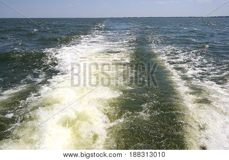 bow wave of fast motor boat on the sea and picturesque blue sky. the view behind the boat