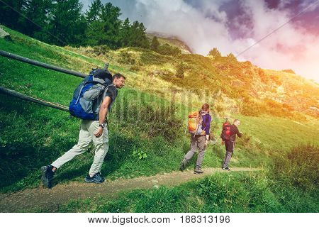thee hikers in the Apls mountains. Trek near Matterhorn mount. hikers on the trail on the alpine meadows hills and frees