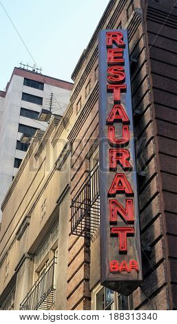 New York City, NY, USA - June 29, 2014. A generic vertical neon red restaurant and bar sign on a street corner in New York City