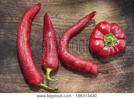 four red hot peppers on the wooden background