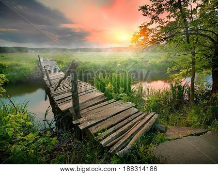 Old wooden bridge through narrow river at sunrise