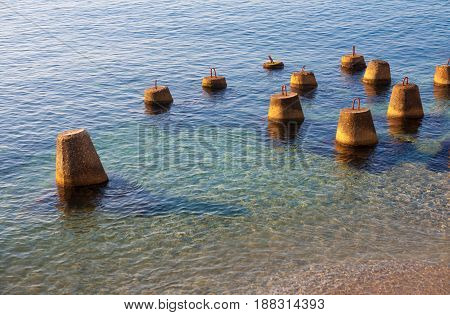 Southern coast of Crimea, calm sea, calm. Clear clear water. At the shore there are protective buns. Color: blue, green, yellow, red.