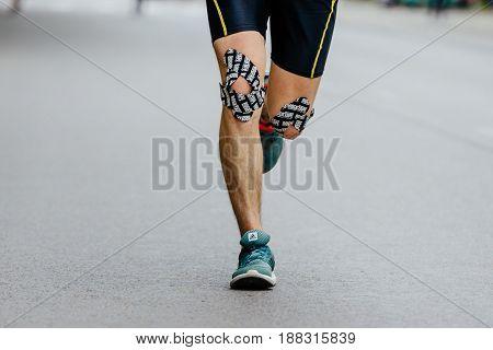 Ekaterinburg Russia - May 21 2017: closeup knees male runner kinesio tape in City half marathon