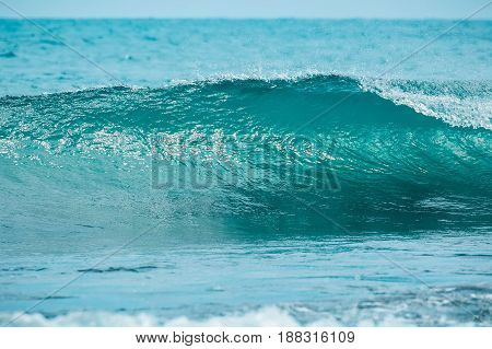 Blue ideal wave in tropical ocean. Wave barrel crashing and clear water.