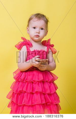 Girl toddler in a pink dress on a yellow background holding a smartphone and looking at the camera.