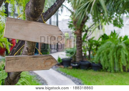 empty wooden signs for text with view of the green garden selective focus