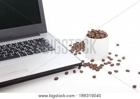 Laptop computer with coffee beans and white coffee cup isolated on white background selective focus copy space
