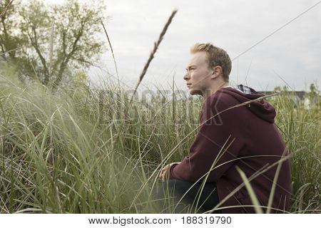 young man in grassy open field thinking and praying