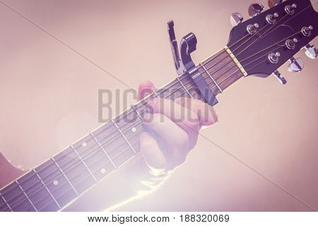 Man's hand plays the guitar with bright lighting around