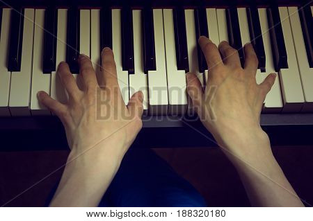 children's hands playing the piano on a dark background