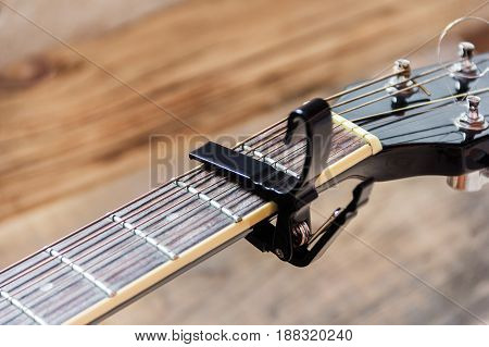 Black capo on a guitar on a wooden background