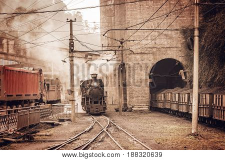 Steam narrow-gauge locomotive stands by the coal loading point. Yuejin. China.