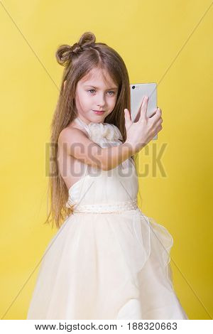 Teenager girl in a dress on a yellow background photographed themselves on the phone.