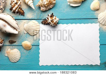 Marine summer postcard. Seashells on blue wooden boards in the sand on the beach