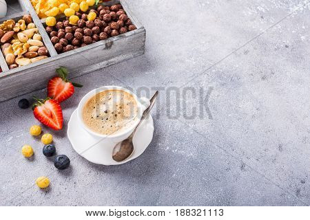 Healthy breakfast with coffee, variety of cold quick breakfast cereals and berries in old gray wooden box, selective focus. Copy space.