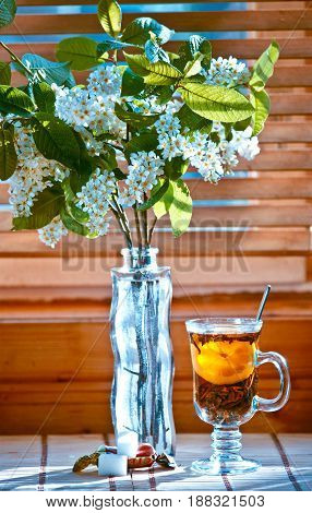 Cup of tea with emon and cherry on wooden background. Window. Spring