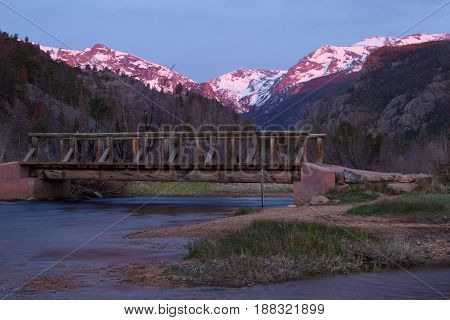 The cub lake trailhead foot bridge crosses The Big Thompson River as the mountains glow at sunrise in Rocky Mountain National Park