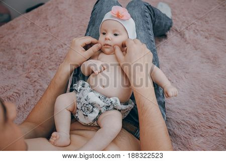 young family at home caring for her baby