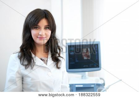 Portrait of professional female nurse in white uniform at modern and new clinic, standing at cabinet, posing, smiling at camera. Attractive brunette doctor against ultrasound equipment and computer.