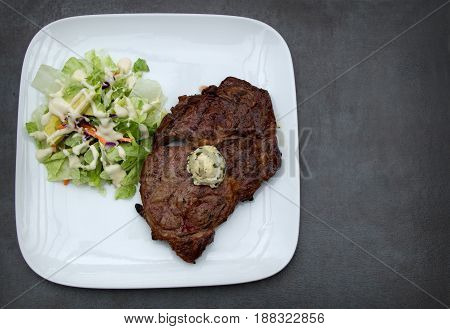 Fat filled Ribeye Steak with Cilantro Butter and a side salad topped with Ranch dressing. Perfect for a ketogenic diet
