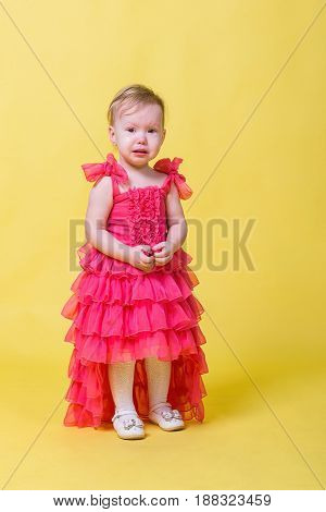 Girl toddler in a pink dress on a yellow background in the Studio.