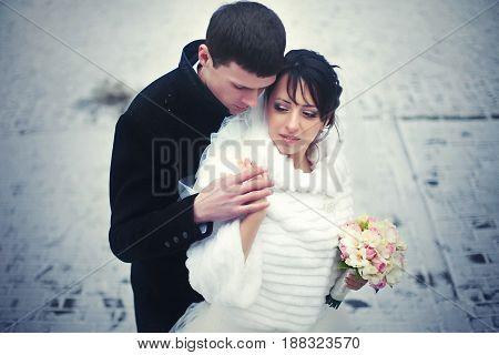 Bride Daydreams Standing In Groom's Hugs Over The Snow