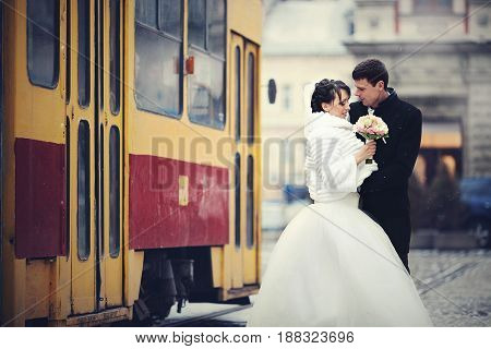 Groom Embraces A Bride In Winter Coat While Tram Drives Behind Them
