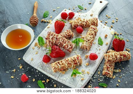 Granola bar with strawberries, raspberry honey and white chocolate on cutting board.