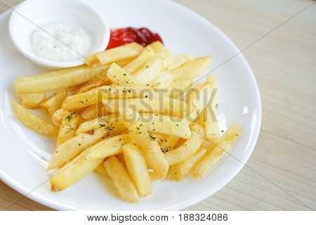 Fresh french fries fried potato sticks parsley topped with ketchup and mayonnaise on white plate