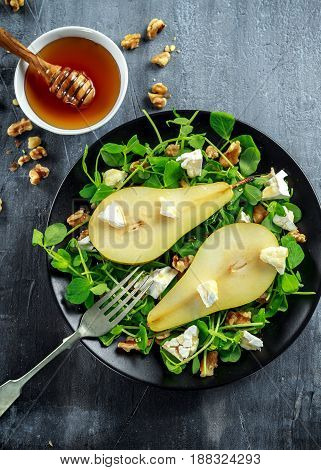 Fresh sweet Pears salad with walnuts, honey and white soft cheese on black plate.