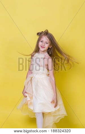 Teenager girl in a dress on a yellow background poses for the camera.