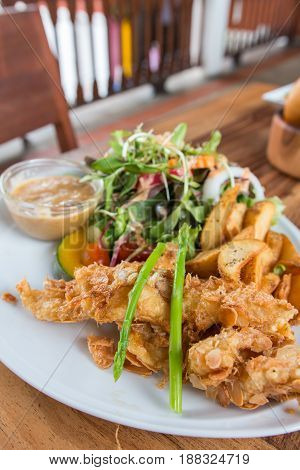 fish and chips served with almond and salad on the white plate